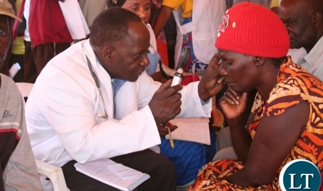 The Ministry of Health in partnership with ORBIS with funding from Standard Chartered Bank organized a free eye screening, provision of spectacles and drug campaign in Solwezi on Thursday. Above, an eye specialist George Chipeta from Solwezi Urban clinic (l) screening Christine Kamuyutwa from Highland compound at Kyawama grounds on Friday as Nurse Dorcas Mulenga(m) looks on