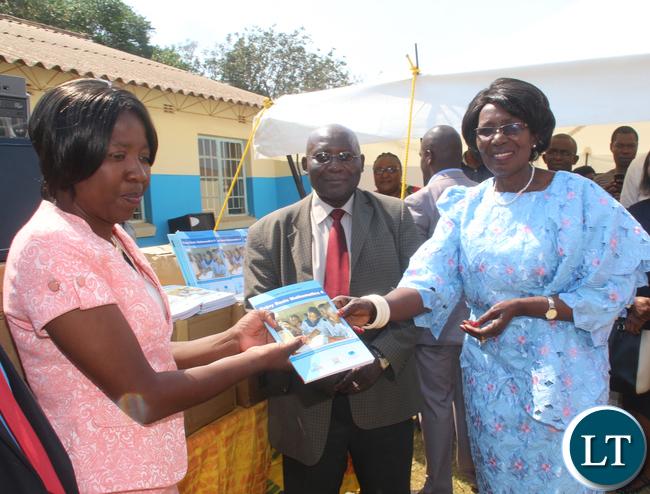 Zambia VEEP Inonge Mutukwa Wina presenting a book sample of her donation to a member of staff