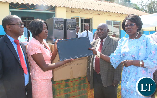 VEEP handing of a book sample to School Head teacher Mrs. Priscilla Sukwa while looking on is Minister of General Education Dr Dennis Wachinga