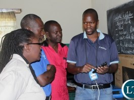 Digital Satellite Television (DSTV) Installer Sebastian Muntanga (r) shows Kanyonyo Secondary School teachers a DSTV Explorer Decoder remote control donated by Multi-Choice Zambia in partnership with Ministry of General Education in a program of installing free DSTV Educational Bouquets in schools in Mongu