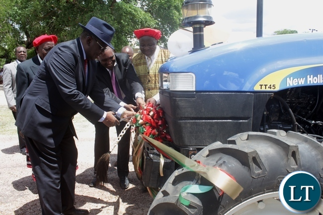 Litunga Imwiko Lubosi II (l) cutting the ribbon during the handing over ceremony of his tractor purchased from DANA Holdings Limited through a loan from National Savings and Credit Bank (NATSAVE) in Limulunga District, Western Province