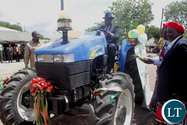 Litunga Imwiko Lubosi II (c) operating his tractor during the handover ceremony of farming equipment purchased from DANA Holdings Limited through a loan from National Savings and Credit Bank (NATSAVE) in Limulunga District, Western Province