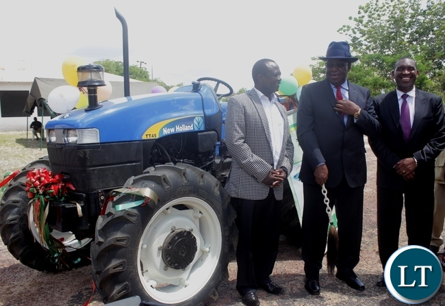 Litunga Imwiko Lubosi II (c) poses for a photograph with DANA Holdings Limited CEO Dr. David Nama (l) and NATSAVE Bank Managing Director Cephas Chabu (r) during the handing over ceremony of his tractor purchased from DANA Holdings Limited through a loan from National Savings and Credit Bank (NATSAVE) in Limulunga District, Western Province