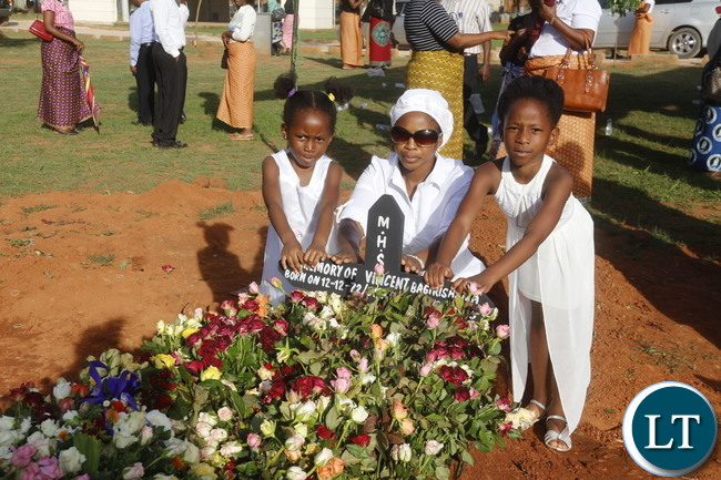 Funeral of the late Rwandian Business Man who was shot dead during the week: Daughters Ishimwe Rosana and Ikuzwe Roswell planting a cross to the grave on their father late Vincent Bagirishema. Picture by Jean Mandela