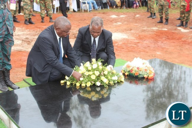 UNCLE to the late Mkhondo Lungu, Newton Lungu (l) and the late's elder brother Japhet, lay a wreath at the grave of Mr. Mkhondo Lungu at his Kachule farm in Lundazi