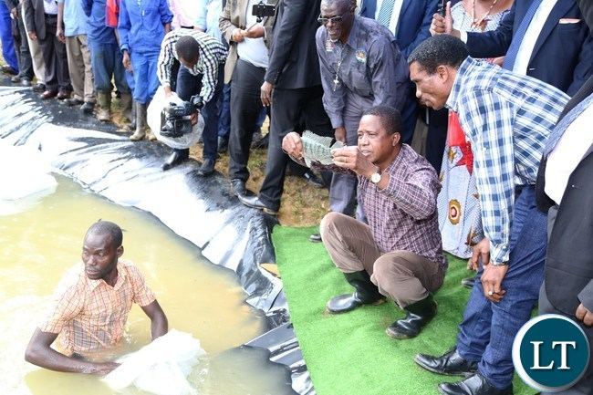 President Edgar Lungu flanked by Livestock and fisheries Minister Michael Katambo (R) admires fish during the restocking of fingerlings at the State Lodge Ponds in lusaka