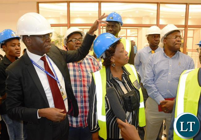 National pension Scheme Authority Director General Yollard Kachinda showing the (NPSA) offices to Minister of Labour Joyce Simukoko during the tour of Society Business Park in Lusaka