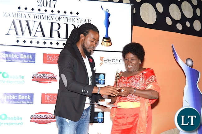 Ken Tonga presents the Cultural Ambassadors award to Judith Mwila during the Afro Multi Media Productions Women of the Year Awards giving Ceremony to mark the International Women's Day Celebrations at Government Complex in Lusaka on Tuesday, March 7,2017 -Picture by THOMAS NSAMA