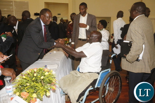 Kaoma based Kacha Football club Jackson Biemba shaking hands with FAZ President Andrew Kamanga at the closure of AGM.