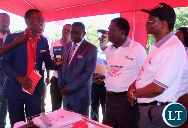 Zanaco Bank Mongu Branch Retail Sales and Service Coordinator Berry Mwansa (l) displays the swiping machine to Rural Finance Expansion Programme (RUFEP) Coordinator Micheal Mbulo (r) Western Province Permanent Secretary Mwangala Liomba (2nd l) and Mongu District Commissioner (2nd r) during the launch of Financial Literacy Week in Mongu