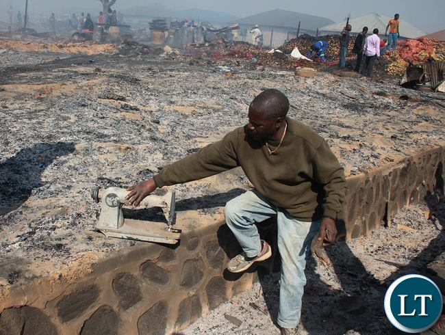 Man picks the remains of his sewing machine he used to make sofas after fire gutted Kapalala Market in Ndola in the early morning hours of today. Sofas were burnt to ashes Pictures-Humphrey Jupite