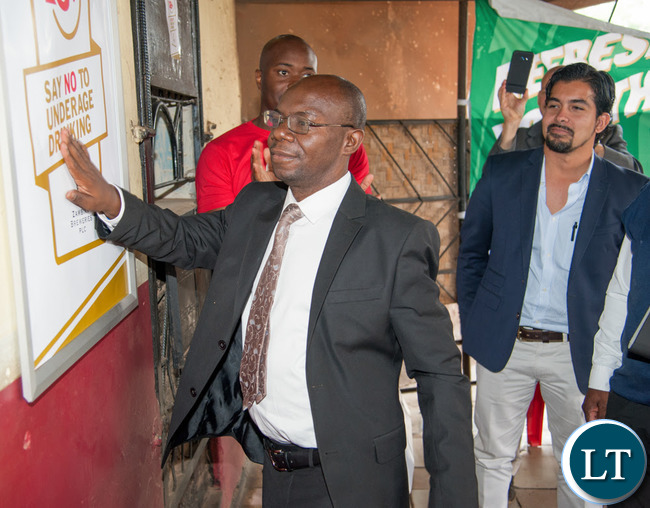 """The Mayor of Lusaka, His Worship Wilson Kalumba puts up the first poster to launch the Zambian Breweries' new """"18Plus SAY NO TO UNDERAGE DRINKING"""" campaign, accompanied by Zambian Breweries Country Director Jose Daniel Moran."""