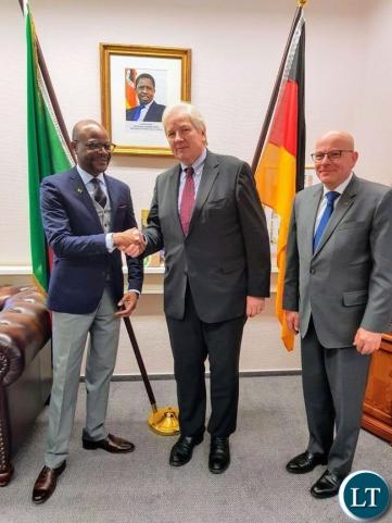 Ambassador Anthony Mukwita shakes hands with CEO of German Africa Business Association Mr. Kannengiesser in grey suit and blue neck-tie and also with Ambassador Kochanke, red neck-tie and dark suit in his office on Axel-Springer-Strasse in Berlin. Picture courtesy of the Embassy of Zambia in Germany.