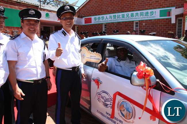 Zambia Police IG Kakoma Kanganji testing one of the cars handed over while looking on are Zambia Police reserve Senior Superintendent Wu Ming (far left) and Zambia Police reserve Assistant Commissioner Zhang Ming (next to the IG) PICTURE BY JEAN MANDELA