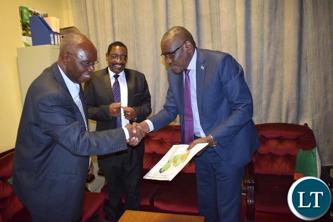 Minister of Tourism and Arts Hon. Charles Banda Banda receiving Barotse Maps from renowned archeologist and author Nicholas Katanekwa.