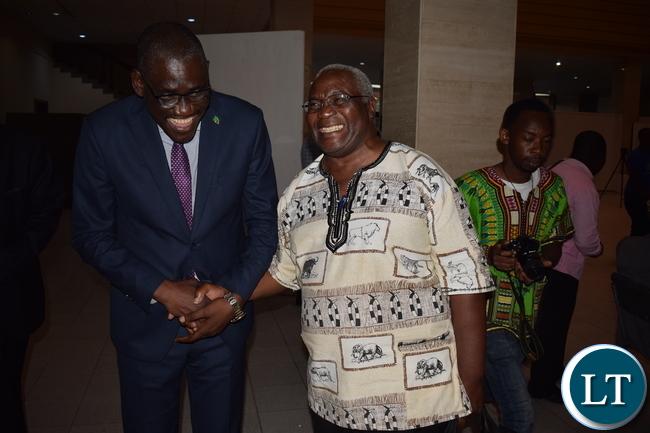 Minister of Tourism and Arts Hon. Charles Banda Banda shares a light Moment with Mr. Akashambatwa- Mbikusita Lewanika at the event.