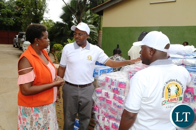 Association of Burundian Residents In Zambia Vice Chairperson Emile Masabarakiza with his Chairperson Dieudonne Baranzira handing over the donated goods to Kabwata Orphanage goods worth K 30,000 to the founder Angela Miyanda during the donation