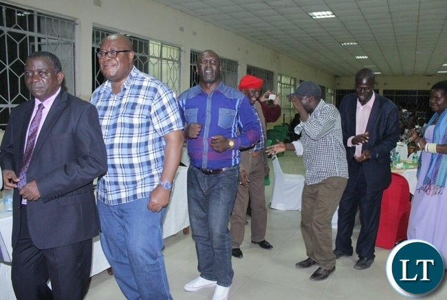 Out-going Western Province Permanent Secretary Mwangala Liomba (l) leads his In-coming counterpart Sibanze Simuchoba (2nd l) in dancing during a Farewell and Welcome party for them in Mongu