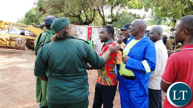Kasama Municipal Deputy Mayor Osward Mukuka (work suit) when a team of Council officers and state security swung into action to demolisheall makeshifts in the central business area in a bid to prevent the outbreak of cholera today.-Picture by Mary Bwembya (ZANIS).