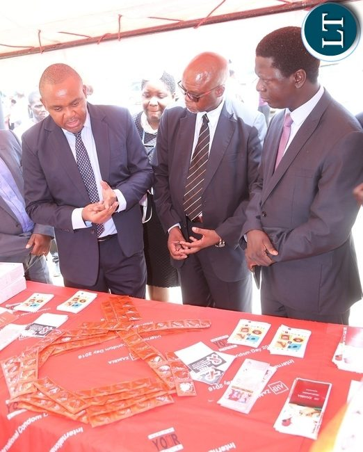 AIDS Heath Foundation Country Director Dr. Mabvuto Kango stress a point on the condoms to Ministry of Health Director Public Health Dr. Andrew Silumesii (r) and Acting Director General National AIDS Council Fortune Chibamba (2nr) during the International Condom Day tour of stands at Central Mall