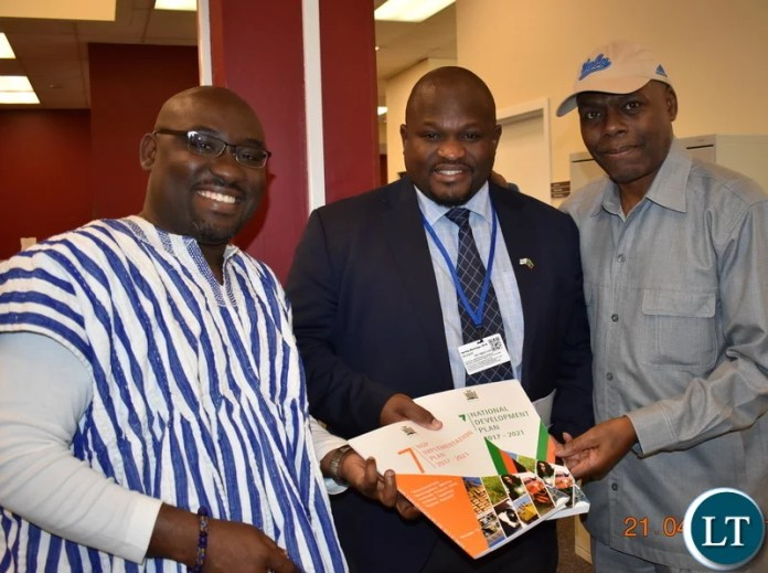 Minister of National Development Planning Alexander Chiteme handing over the Seventh National Development Plan (7NDP) to Voice of America (VOA) veteran broadcast and host of Straight Talk Africa Shaka Ssali and Nightline Africa host Peter Clottey in Washington DC, USA, on Saturday 21 April 2018. PHOTO   CHIBAULA D. SILWAMBA   MNDP