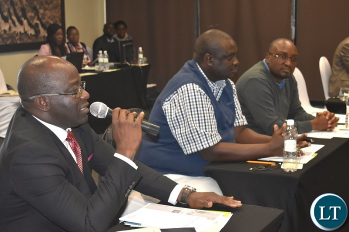 Ministry of National Development Planning (Director – Monitoring and Evaluation) Mr. Chola Chabala (left) speaking at the national consultative stakeholder meeting on setting up the National Climate Change Fund (NCCF) in Livingstone on Monday 18 June 2018. On his left of Director Development Planning Mr. Mulele Mulele and Permanent Secretary Development Planning and Administration Mr. Chola Chabala. PHOTO | CHIBAULA D. SILWAMBA | MNDP