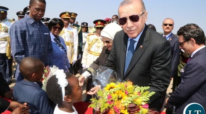 Recep Tayyip Erdogan President of the Republic of Turkey receives a bouquet of f lowers from 7 year old girl Temwani Mponela at Kenneth Kaunda International Airport.