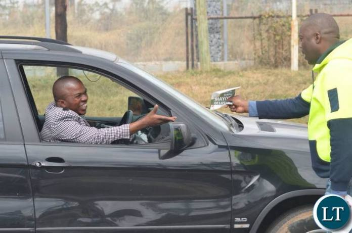 Lusaka Province Minister Bowman Lusambo hands out a flyer as he campaigns for Miles Sampa along the Great East Road