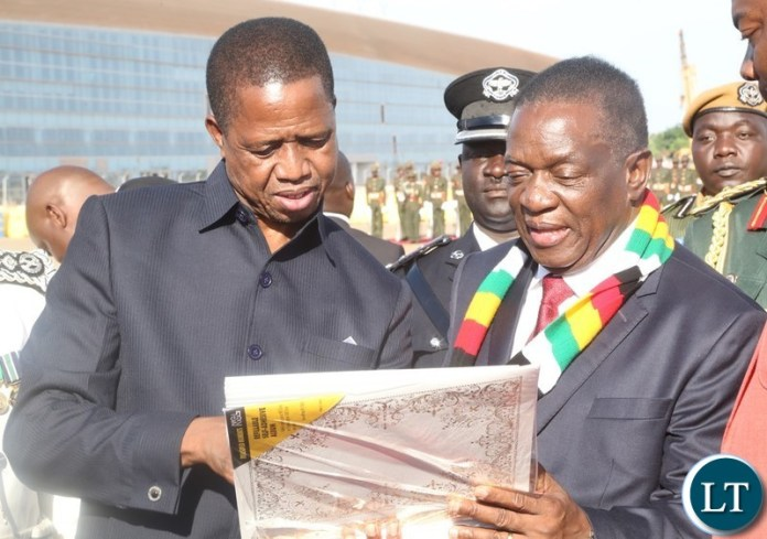 President Edgar Lungu shows pictures to President of Zimbabwe Emmerson Dambudza Mnangagwa shortly before handing over the Presidential photo album to him at Kenneth Kaunda International Airport before his departure