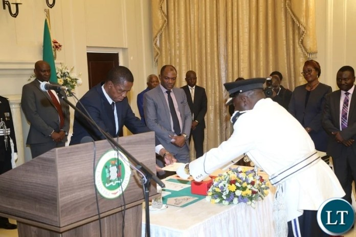 President Edgar Lungu receives the latter of Oath from the newly appointed Southern Province Police Commissioner Diamond Likashi during swearing in ceremony at State House