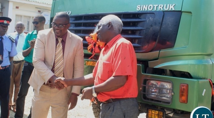 Western Province Deputy Permanent Secretary Bernard Chomba (l) congratulates Mongu Mayor Akayombokwa Kusiyo (r) shortly after handing over a truck to Mongu Municipal Council for garbage collection at a total cost of k784, 200.80 in Mongu, Western Province.
