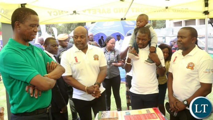 President Edgar Lungu confers with RTSA Staff at the Stand of Road Transport Safety Agency Stand during the tour of stands at the commemoration of 2018 International Anti-Corruption Day at Show grounds