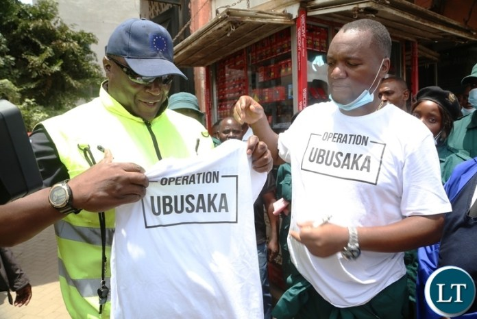 Lusaka Mayor Miles Sampa and Mr. Mwewa admires Ubusaka T-shirt shortly after receiving it from Lusaka mayor at Samson building during the Cleaning of the Central Business District under the theme Ubusaka