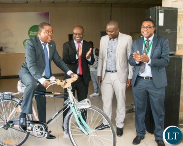 Transport and Commmunications Permanent Secretary Eng. Misheck Lungu tries out one of the bicycles during the hand over ceremony at Zamtel House