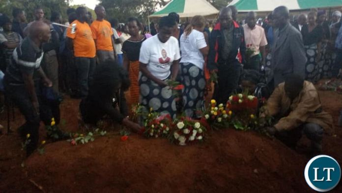 Family members lay flowers on the grave of Mr Kasongo at Memorial Park on Saturday evening.