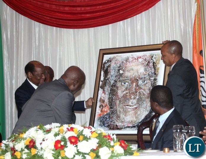 Mozambique former President Joaquim Chissano presenting a painting gift to Zambia 1st president Kenneth Kaunda  on behalf of Africa Forum while looking are president Edgar Lungu and assistant to former Mozambique president Tomas de Sousa  Mabuiangue