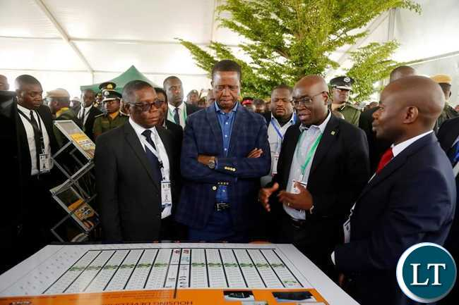 President Edgar Chagwa Lungu centre listens to NAPSA Director General Yollard Kachinda second from right as he explains on the Solwezi 400 Housing Units which the company will construct This was at Solwezi City Hall during the North West Expo on Monday August 192019 PICTURE BY SALIM HENRYSTATE HOUSE 2019