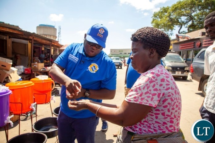 Peoples Alliance for Change President Andyford Banda distributing hand wash basins to Marketeers