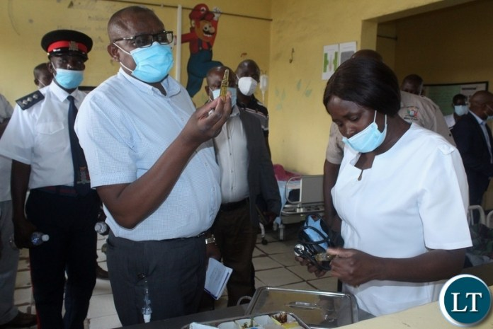Ministry of Health Technical Services Permanent Secretary Dr. Kennedy Malama (l) checking the drugs on Lewanika General Hospital Children's Ward nurse NawaMonde's (r) tray during visiting of health facilities in Mongu
