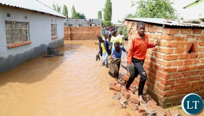Same Mumbwa residents walk off there submerged house hopeless after the Kandesha dam burst it banks causing the flash floods yesterday. Sunday, December 27, 2020. Picture by ROYD SIBAJENE/ZANIS