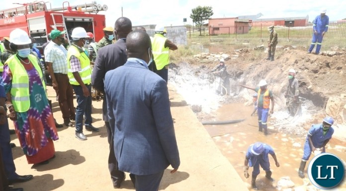 Vice President Inonge Wina flanked by DMMU National Coordinator Chanda Kabwe inspecting the drainage system being built to help flooding off Kanyama area at road 55