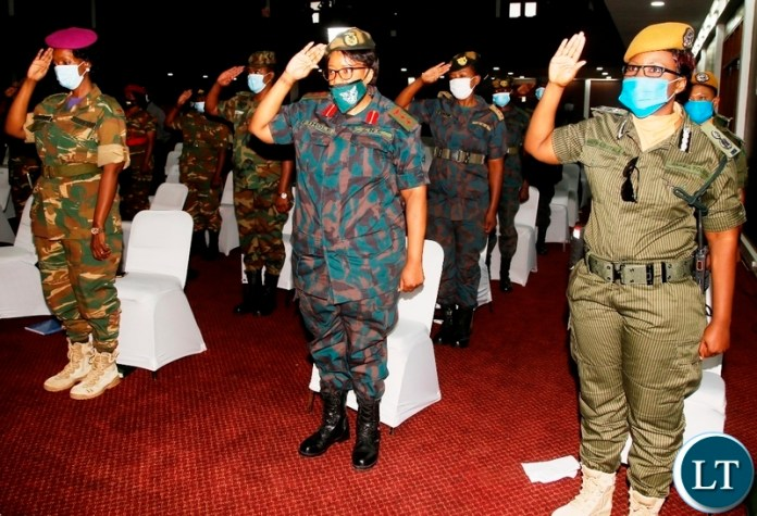 Women in uniform from the security wings salute as they sing the National Anthem during the commemoration of this years International womens day at Mulungushi Conference centre in Lusaka Picture by SUNDAY BWALYAZANIS