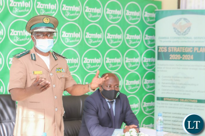 Zambia Correctional Service Commissioner General Dr Chisela Chileshe speaking during the signing ceremony as Zamtel CEO Sydney Mupeta listens on