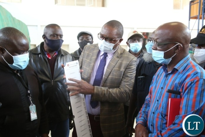 Electoral Officer ,Alick Chakawa showing Political party stakeholders Presidential ballot papers during the verification of 2021 general election in Lusaka.