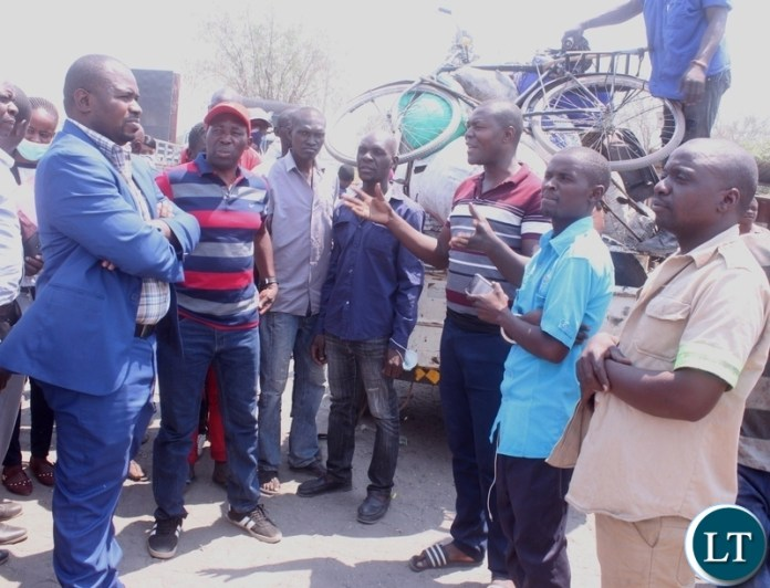 A driver at Mongu Central Market Kelvin Mukumbuta (gesture) appealing to Mongu Mayor Nyambe Matakala (blue suit) not to entertain criminals in markets shortly before addressing the marketeers in Mongu Western Province