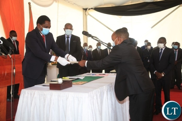 PRESIDENT Hakainde Hichilema receives an affidavit form from Newly sworn in Southern Province Minister,Cornelius Mweetwa at swearing -in ceremony in Lusaka