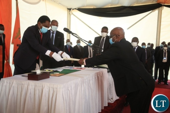 PRESIDENT Hakainde Hichilema receives an affidavit form from Newly sworn in Minister of Lands Richard Muchima at swearing -in ceremony in Lusaka.