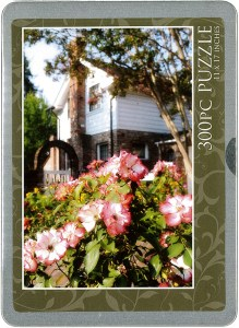 cover of the tin containing a puzzle featuring roses and Luther Burbank's home