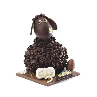 Frisoton noir : 57 € le sujet de 250g Sujet à dominante de chocolat noir ; chocolat au lait et chocolat ivoire. Agneau en chocolat noir Frisoton, pelote de laine et socle de terre en chocolat. OEuf praliné. Pâquerettes en pain azyme recouvert de chocolat ivoire. Amandes hachées. Garniture de pâques. Dimensions : L 12 cm x l 12 cm x h 14 cm