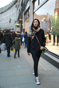 Chinese model Liu Wen wearing a Burberry monogrammed scarf and pre-SS15 black coat, as well as carrying the mini Bee Bag in London on Jan 11th.
